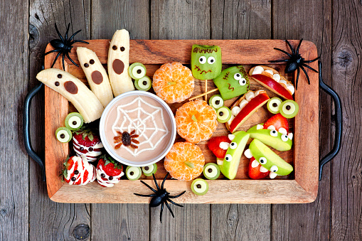 Tray of healthy Halloween fruit snacks, top view over a rustic wood background 1172825767