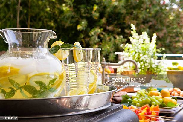 Tray of lemonade on table full of colorful food