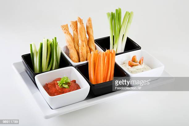 Tray of vegetable sticks with savoury straws and dips, close-up