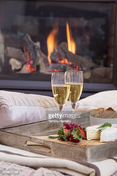 Tray with champagne flutes on sofa, fireplace in background