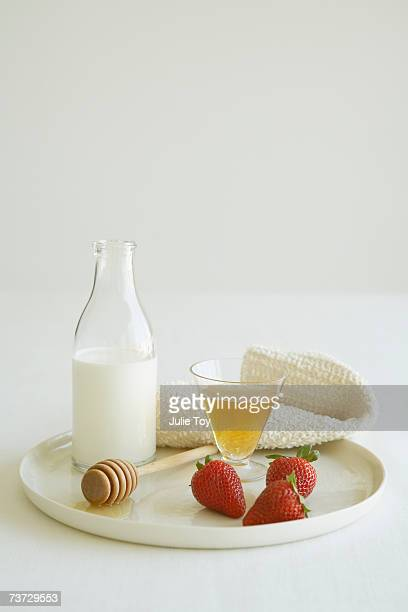 Tray with milk, honey and strawberries, close-up