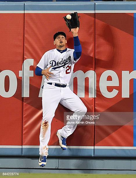 Trayce Thompson of the Los Angeles Dodgers makes a catch at the wall off Brandon Barnes of the Colorado Rockies in the fifth inning of the game at...