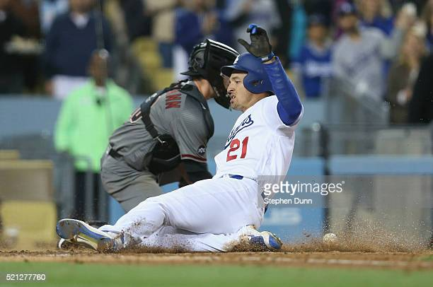 Trayce Thompson of the Los Angeles Dodgers slides home with a run in the seventh inning ahead of the throw to catcher Chris Herrmann of the Arizona...