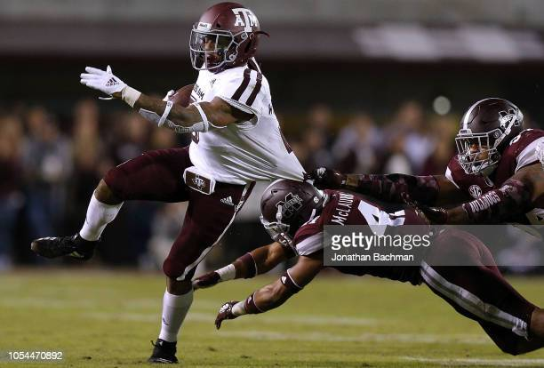 Trayveon Williams of the Texas AM Aggies runs with the ball as Jeffery Simmons and Mark McLaurin of the Mississippi State Bulldogs defend during the...