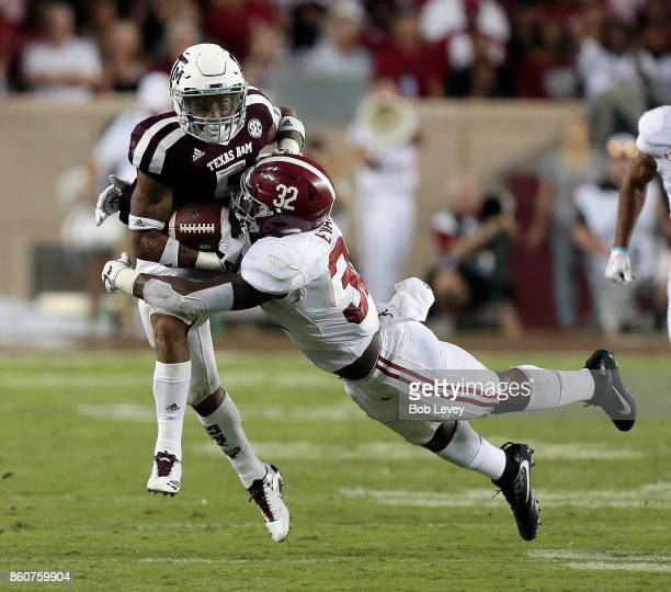 Trayveon Williams of the Texas AM Aggies runs with the ball as Rashaan Evans of the Alabama Crimson Tide and Minkah Fitzpatrick attempt to tackle at...