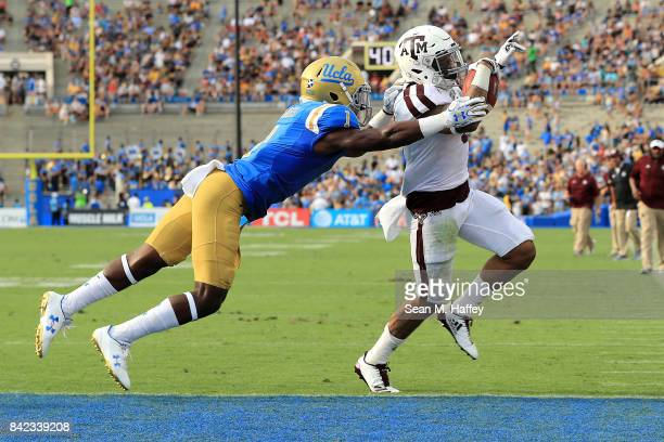 Trayveon Williams of the Texas AM Aggies rushes for a touchdown as Darnay Holmes of the UCLA Bruins defends during the first half of a game at the...