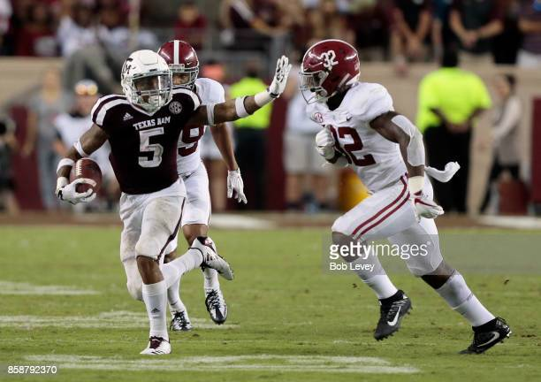 Trayveon Williams of the Texas AM Aggies sticks out his arm to hold off Rashaan Evans of the Alabama Crimson Tide at Kyle Field on October 7 2017 in...