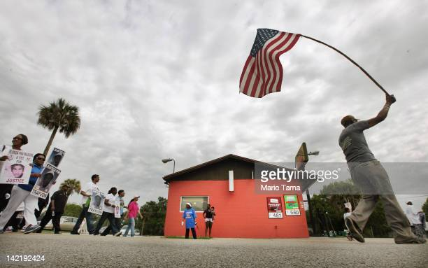 Trayvon Martin supporter Robert Elliott holds an American flag as others prepare to march at Crooms Academy, founded in 1926 as Seminole County's...