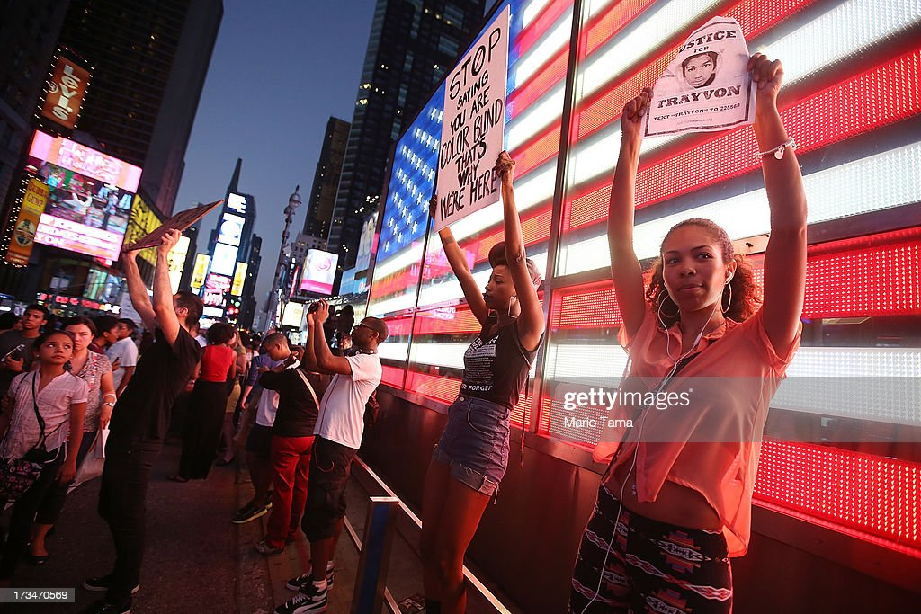 Trayvon Martin supporters stand in front of a lighted American flag in Times Square after marching from a rally for Martin in Union Square in Manhattan on July 14, 2013 in New York City. George Zimmerman was acquitted of all charges in the shooting death of Martin July 13 and many protesters questioned the verdict.