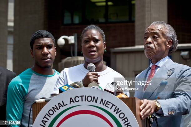 Trayvon Martin's mother Sybrina Fulton speaks at a podium as Trayvon Martin's brother Jahvaris Fulton and Rev. Al Sharpton attend a rally honoring...