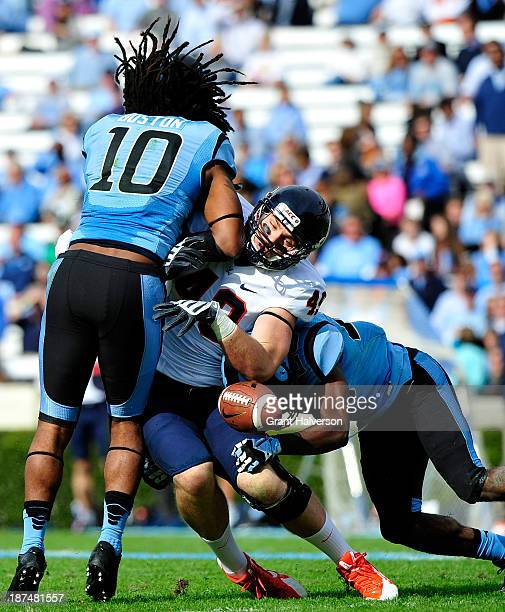 Tre Boston and Dominique Green of the North Carolina Tar Heels break up a pass intended for Zachary Swanson of the Virginia Cavaliers during play at...