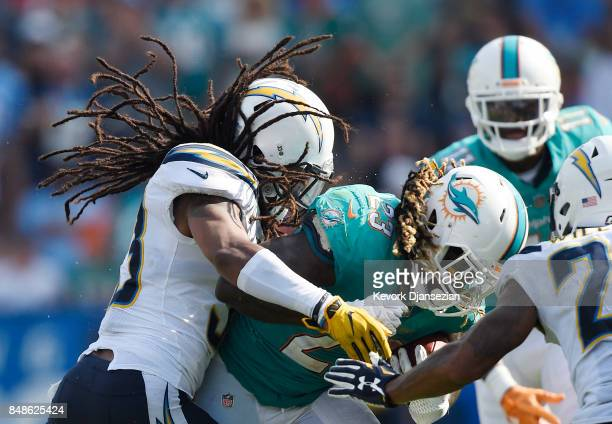 Tre Boston of the Los Angeles Chargers tackles running back Jay Ajayi of the Miami Dolphins during the NFL game at the StubHub Center September 17 in...