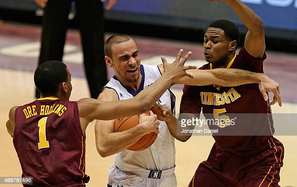 Tre Demps of the Northwestern Wildcats tries to drive between Andre Hollins and Daquein McNeil of the Minnesota Golden Gophers at WelshRyan Arena on...