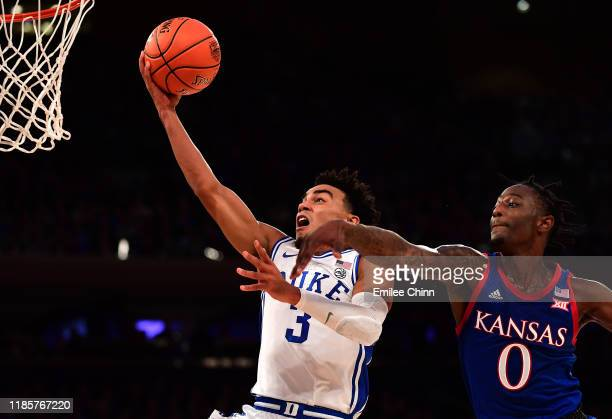 Tre Jones of the Duke Blue Devils goes in for a layup while being guarded by Marcus Garrett of the Kansas Jayhawks in the first half of their game at...