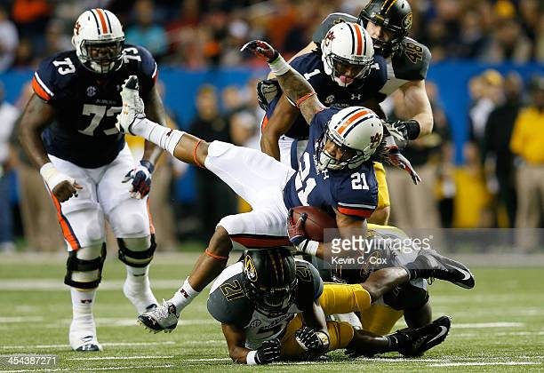 Tre Mason of the Auburn Tigers is upended by Ian Simon of the Missouri Tigers during the SEC Championship Game at Georgia Dome on December 7 2013 in...