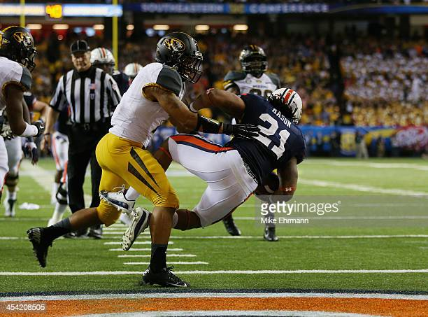 Tre Mason of the Auburn Tigers score a fourth quarter touchdown against Randy Ponder of the Missouri Tigers during the SEC Championship Game at...