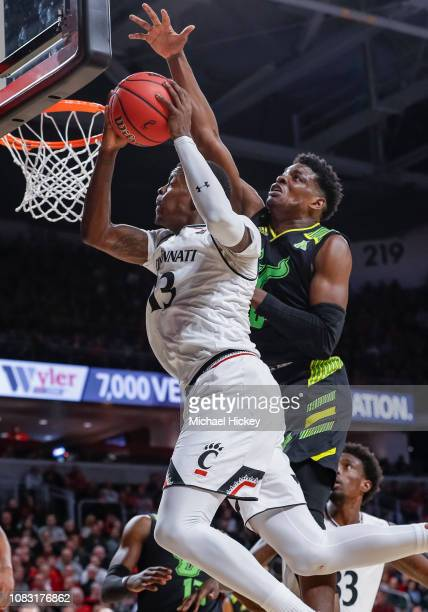 Tre Scott of the Cincinnati Bearcats shoots the ball against Alexis Yetna of the South Florida Bulls during the second half of the game against the...