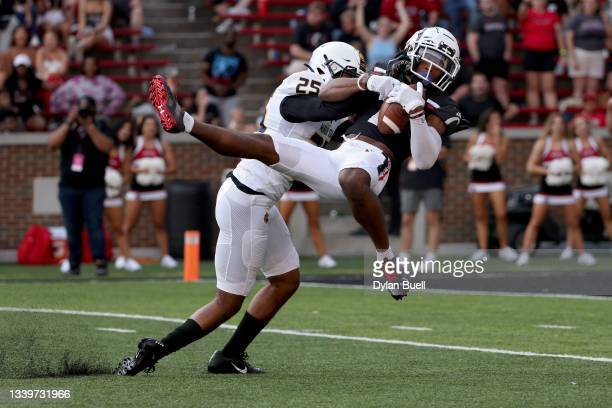Tre Tucker of the Cincinnati Bearcats makes a catch while being defended by Frank Coppet of the Murray State Racers in the fourth quarter at Nippert...