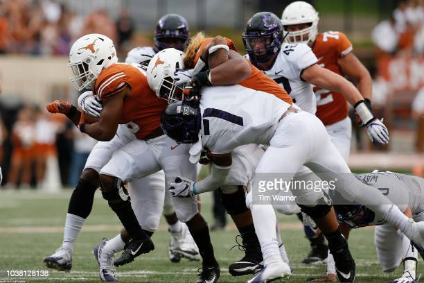 Tre Watson of the Texas Longhorns carries the ball as Patrick Vahe blocks Arico Evans of the TCU Horned Frogs in the second half at Darrell K...
