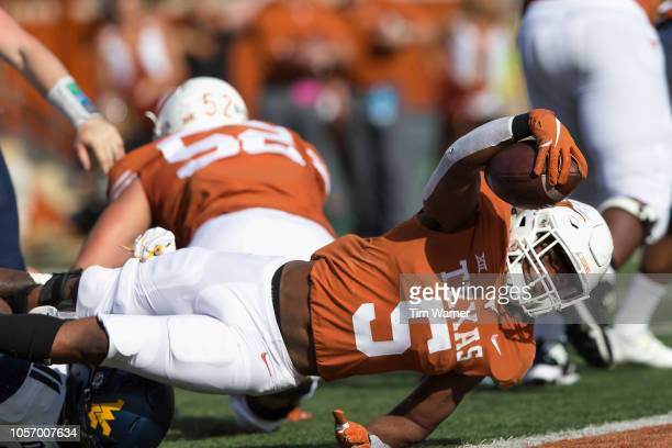 Tre Watson of the Texas Longhorns extends the ball over the goal line for a touchdown in the second quarter against the West Virginia Mountaineers at...