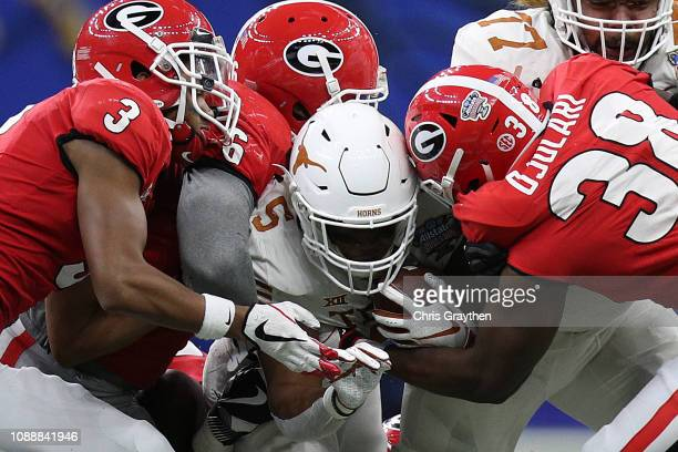 Tre Watson of the Texas Longhorns is tackled by Azeez Ojulari of the Georgia Bulldogs during the Allstate Sugar Bowl at MercedesBenz Superdome on...