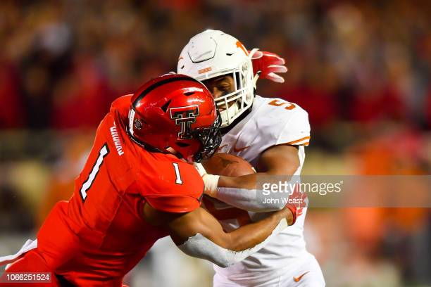 Tre Watson of the Texas Longhorns is tackles by Jordyn Brooks of the Texas Tech Red Raiders during the game on November 10 2018 at Jones ATT Stadium...