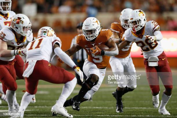Tre Watson of the Texas Longhorns rushes the ball in the second quarter defended by Lawrence White of the Iowa State Cyclones and Anthony Johnson at...