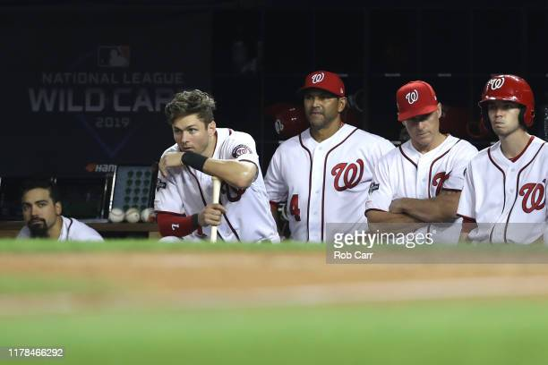 Trea Turner and manager Dave Martinez of the Washington Nationals look on from the dugout against the Milwaukee Brewers during the eighth inning in...