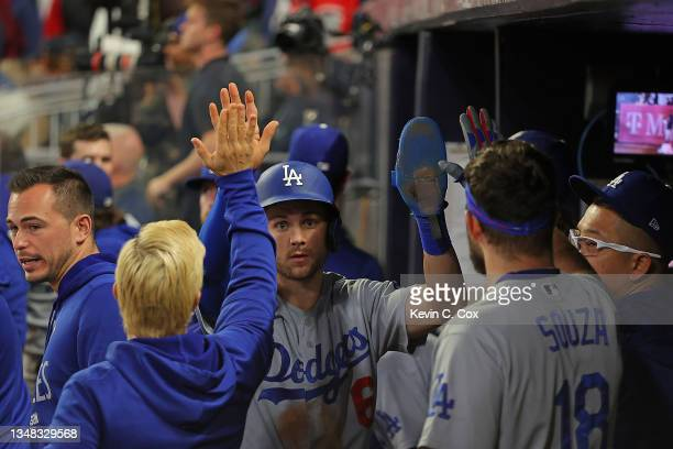 Trea Turner of the Los Angeles Dodgers is congratulated by teammates after scoring on an RBI single by Cody Bellinger during the fourth inning of...