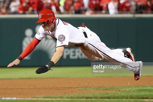Trea Turner of the Washington Nationals dives into third base against the Los Angeles Dodgers in the third inning during game five of the National...