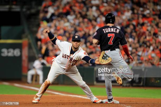 Trea Turner of the Washington Nationals is called out on runner interference for colliding with Yuli Gurriel of the Houston Astros during the seventh...