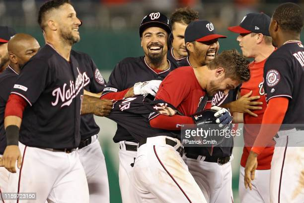 Trea Turner of the Washington Nationals is mobbed by teammates after hitting a gamewinning RBI double against the Miami Marlins during the bottom of...