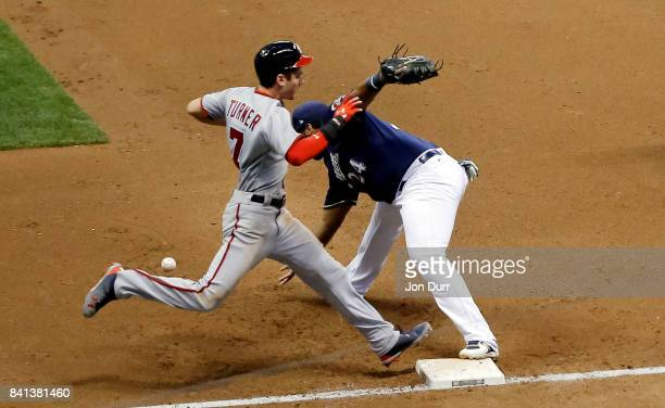 Trea Turner of the Washington Nationals is safe at first on a bunt as Jesus Aguilar of the Milwaukee Brewers takes the throw during the fifth inning...