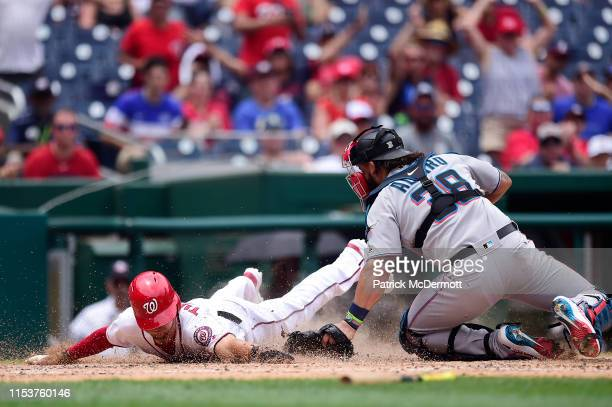 Trea Turner of the Washington Nationals is safe at home plate against Jorge Alfaro of the Miami Marlins on a two run RBI double by Gerardo Parra in...
