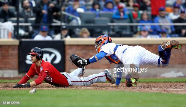 Trea Turner of the Washington Nationals slides home safely in the fifth inning as Rene Rivera of the New York Mets is unable to make the tag on April...