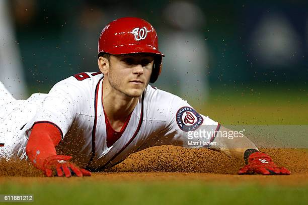 Trea Turner of the Washington Nationals slides safely into third base after hitting a triple in the third inning against the Miami Marlins at...