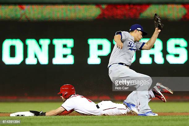Trea Turner of the Washington Nationals steals to second base past Corey Seager of the Los Angeles Dodgers in the third inning during game five of...