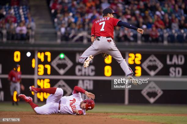 Trea Turner of the Washington Nationals tries to turn a double play against Brock Stassi of the Philadelphia Phillies in the bottom of the first...
