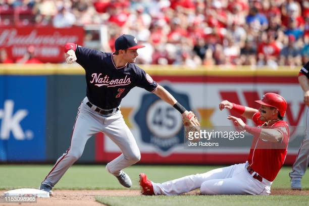 Trea Turner of the Washington Nationals turns a double play ahead of the sliding Derek Dietrich of the Cincinnati Reds with bases loaded in the first...