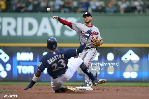 Trea Turner of the Washington Nationals turns a double play past Keon Broxton of the Milwaukee Brewers in the first inning at Miller Park on July 23...