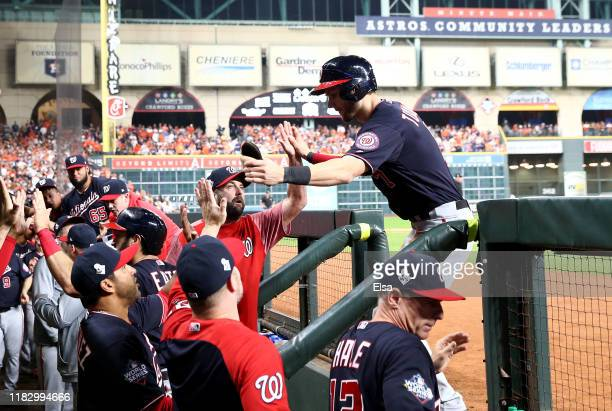 Trea Turner the Washington Nationals is congratulated by his teammates after scoring a run against the Houston Astros during the first inning in Game...