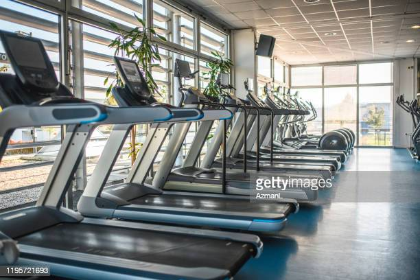 treadmills and cross trainers side by side in gym - leisure facilities stock pictures, royalty-free photos & images