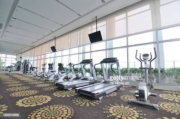 Treadmills and ellipticals by the windows of a health club