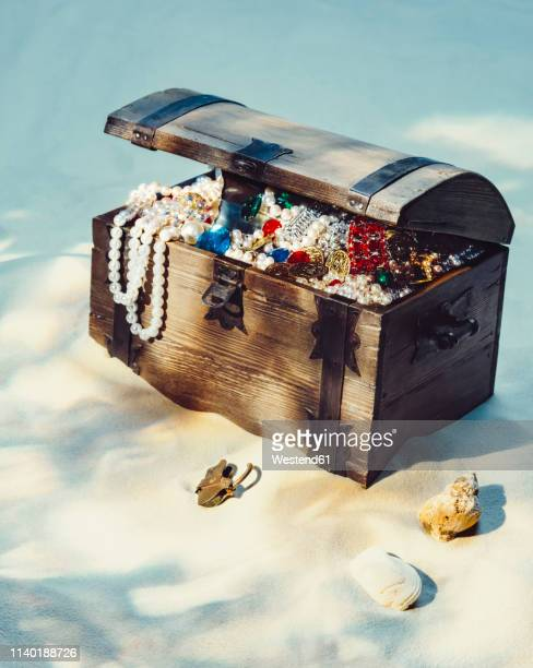 treasure chest filled with jewels and gold coins on sandy beach - 宝箱 ストックフォトと画像