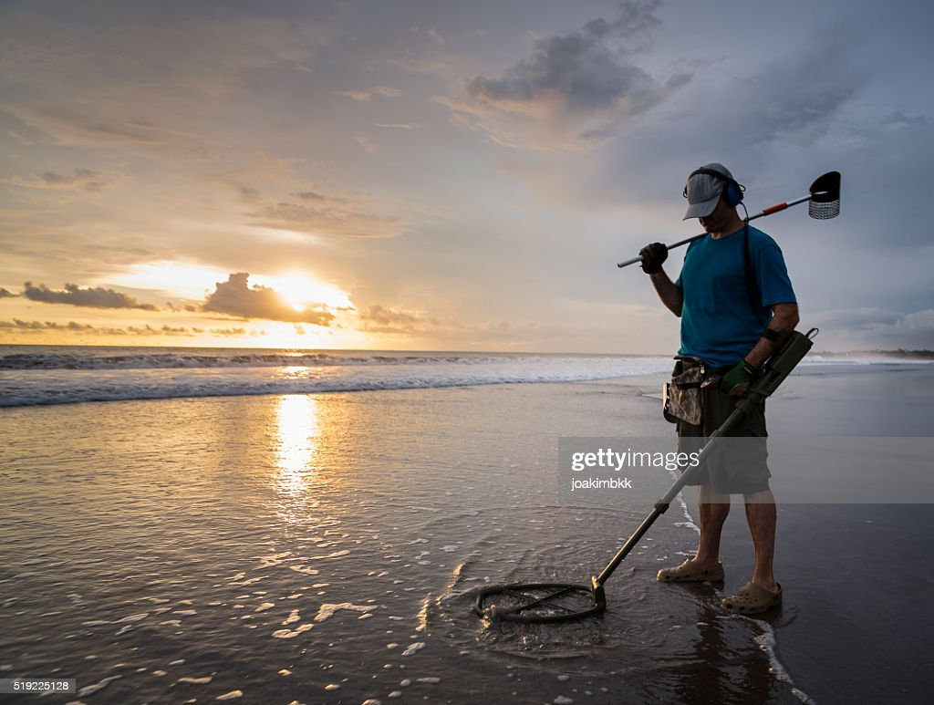 Treasure hunter on the beach with a metal detector : Stock Photo