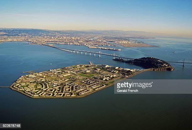 treasure island aerial in san francisco bay with oakland-san francisco bay bridge in background - treasure island california stock pictures, royalty-free photos & images