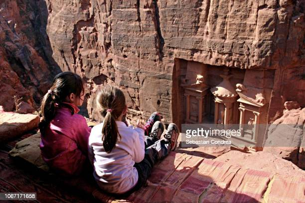 Treasury from above with a two sisters, seated on a cliff, Al Khazneh in the ancient city of Petra, Jordan