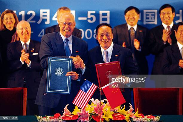 Treasury Secretary Henry Paulson and Chinese Vice Premier Wang Qishan trade agreements and shake hands at the Eco Partnership signing ceremony during...