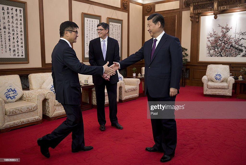 U.S. Treasury Secretary Jack Lew (C) looks on as President Xi Jinping (R) shakes hands with U.S Ambassador to China Gary Locke (C) before their meeting at the Diaoyutai State Guesthouse on November 15, 2013 in Beijing, China.
