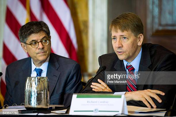 Treasury Secretary Jacob J Lew looks on as Director of the Consumer Financial Protection Bureau Richard Cordray delivers remarks during a public...